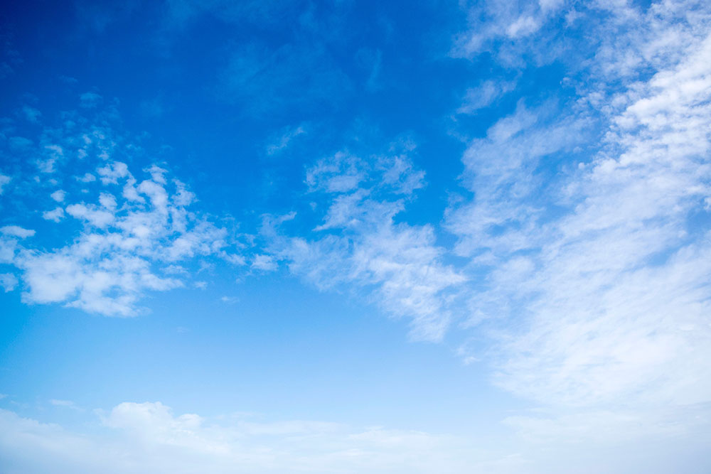 A photo shows a blue sky with light scattered clouds.