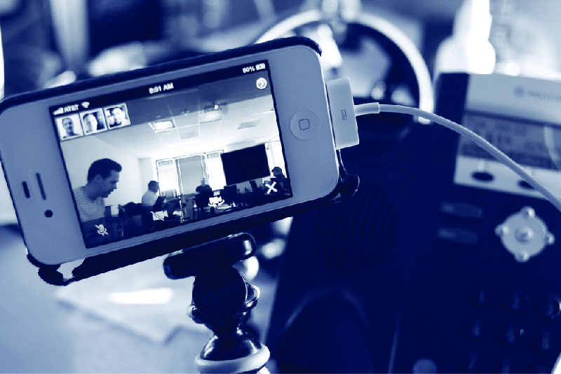 This photo shows a smartphone set up on a tripod for a video conference.