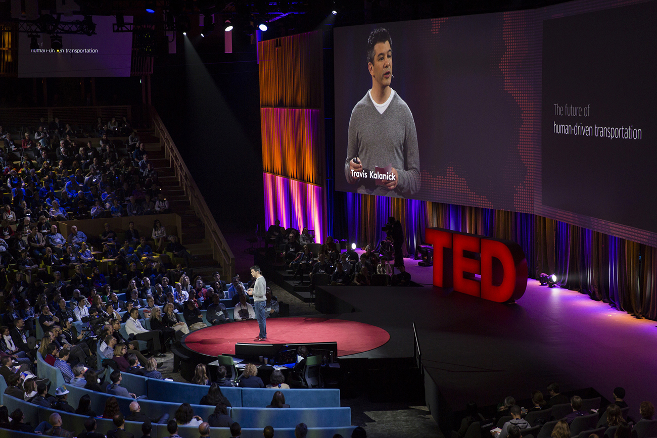 A photo shows Travis Kalanick talking to a large audience during a TED talk.
