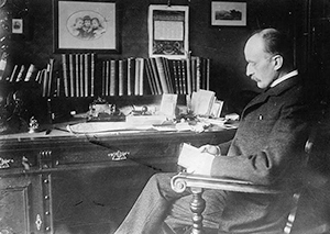 A photo of Max Planck sitting at a desk is shown. The photo is taken from his side and he appears to be reading a document.