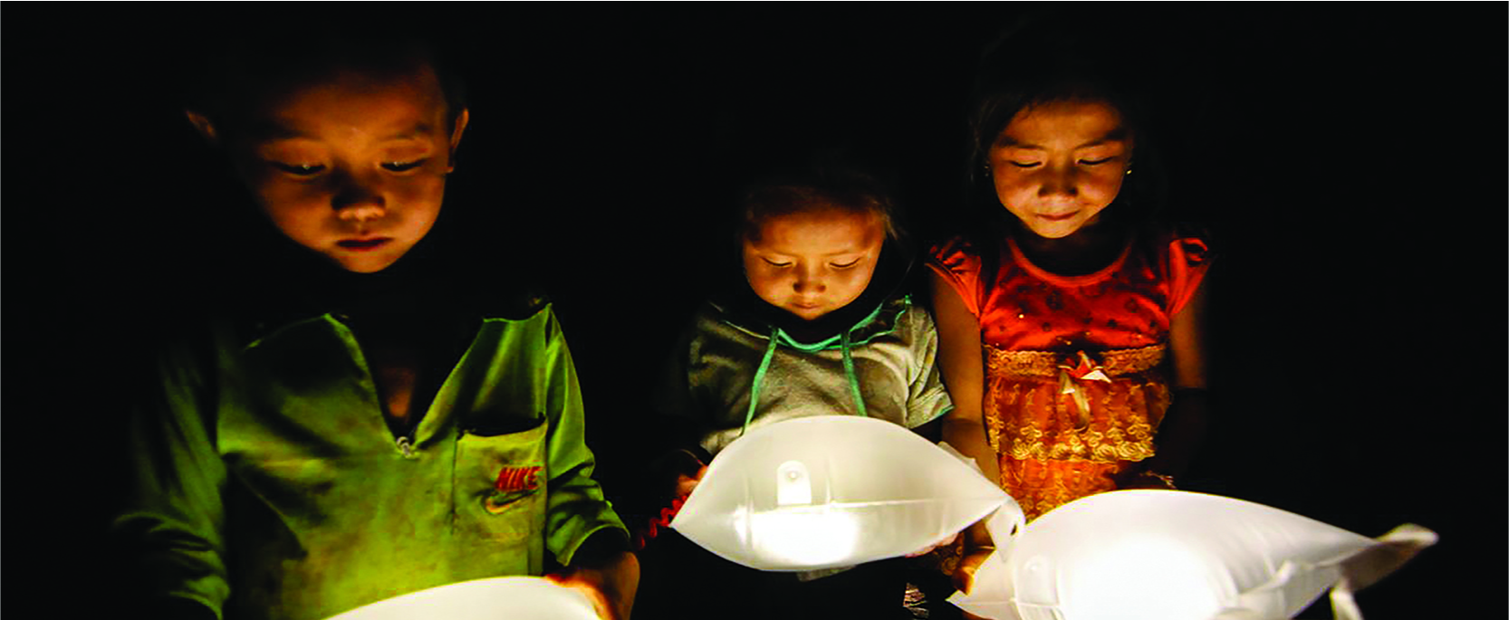 Three children hold white pillow-like objects that emanate light.