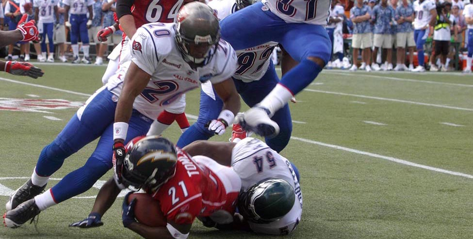 A photograph shows a football game with four football players trying to tackle a fifth player. A crowd is shown in the background.