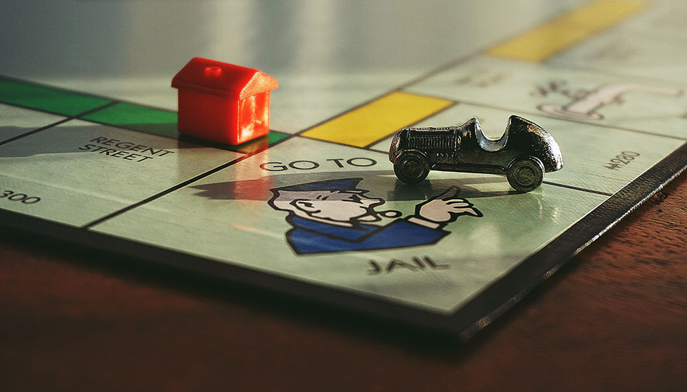 A photo shows the board game Monopoly in which the car game piece has landed on the GO TO JAIL space.