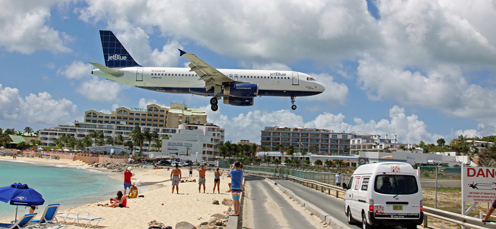 An airplane is flying over a beach area in St. Maarten as it comes in for a landing at the airport. The airplane's acceleration is in the opposite direction of its velocity.