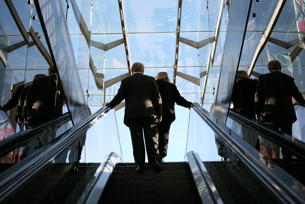 A man and a woman, both wearing business suits, are shown from behind at the top of an escalator