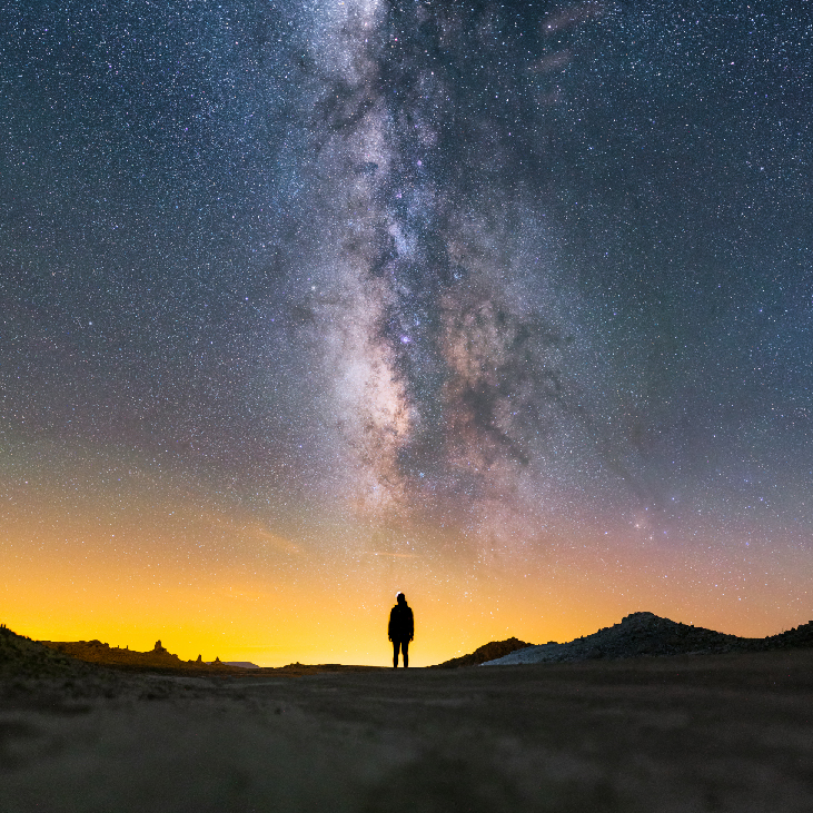 Image of the night sky showing the Milky Way, a dense, vertical band of stars. Under the Milky Way is the silhouette of a person.
