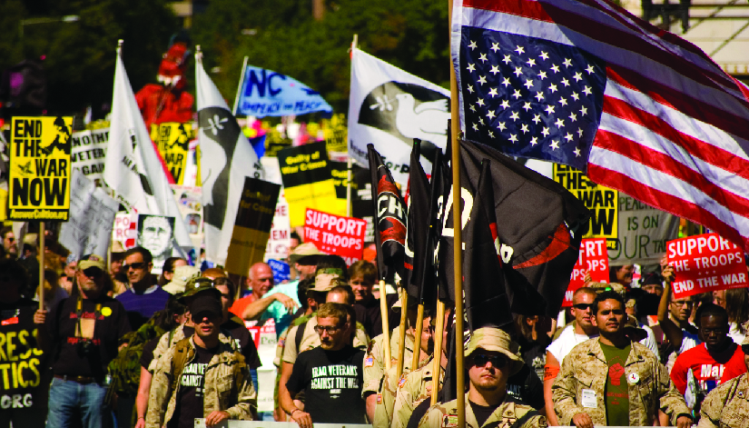"An image of a group of people, several of whom are holding flags and signs. One of the signs reads ""End the war now"", and another reads ""Support the troops, end the war""."