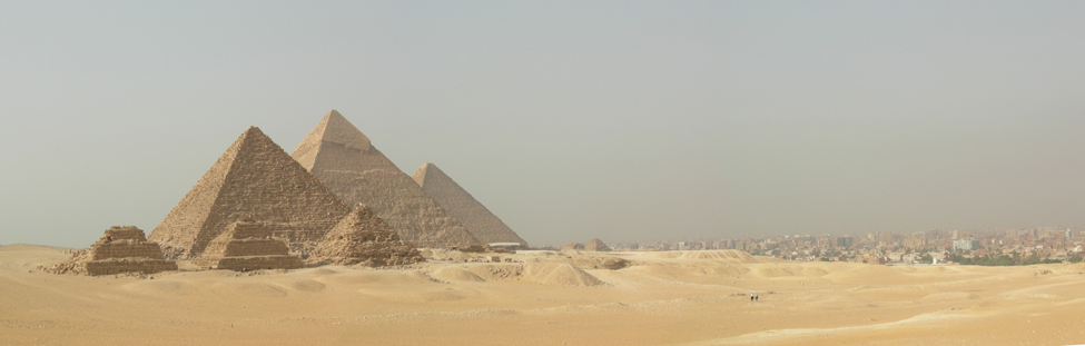 Photo of the Egyptian pyramids near a modern city.