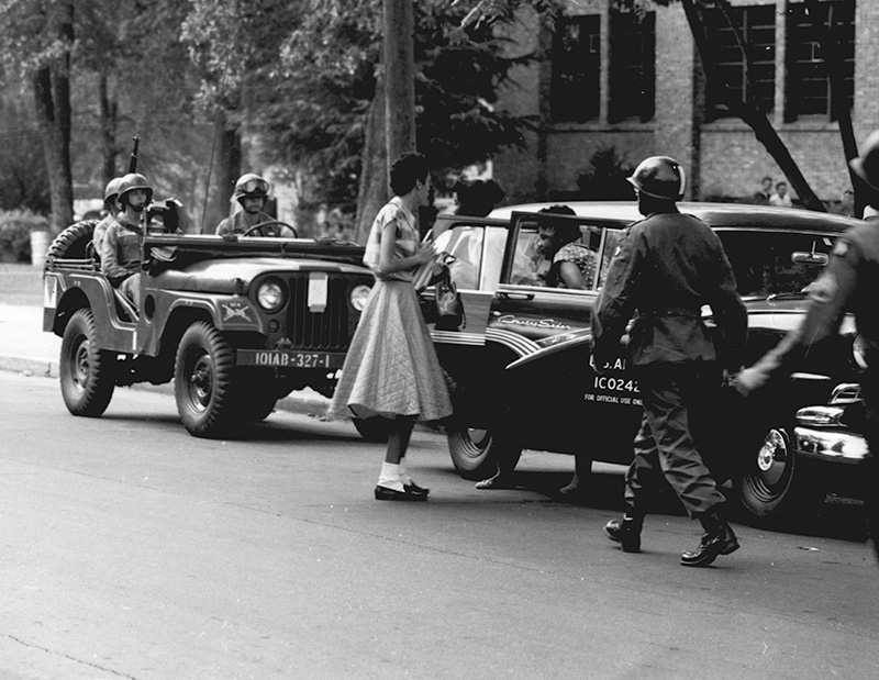 A black-and-white photo shows African-American students arrive at Central High School in Little Rock in army vehicles, escorted by soldiers from the 101 Airborne Division.