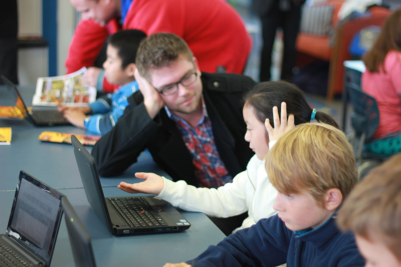 A photo shows mid-adult male teachers helping young students to use laptops.