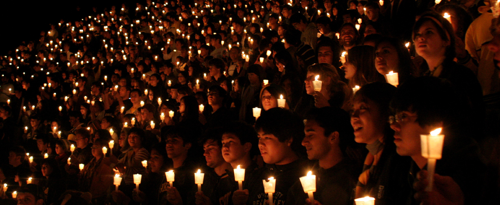 A photo shows a massive group of young girls and boys holding candles at a vigil.