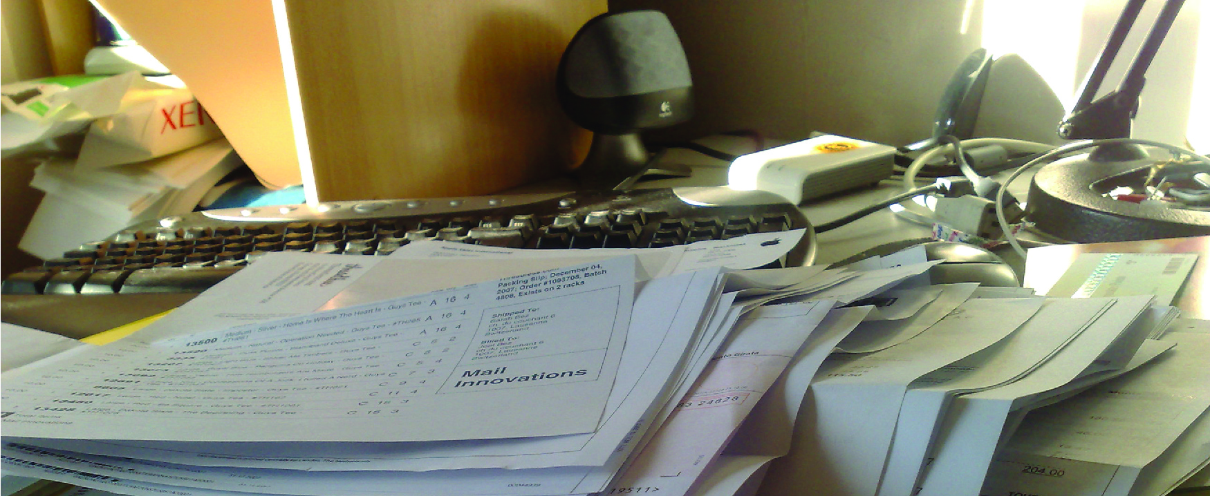 A photograph of a messy desk piled with papers, a computer keyboard in the background.