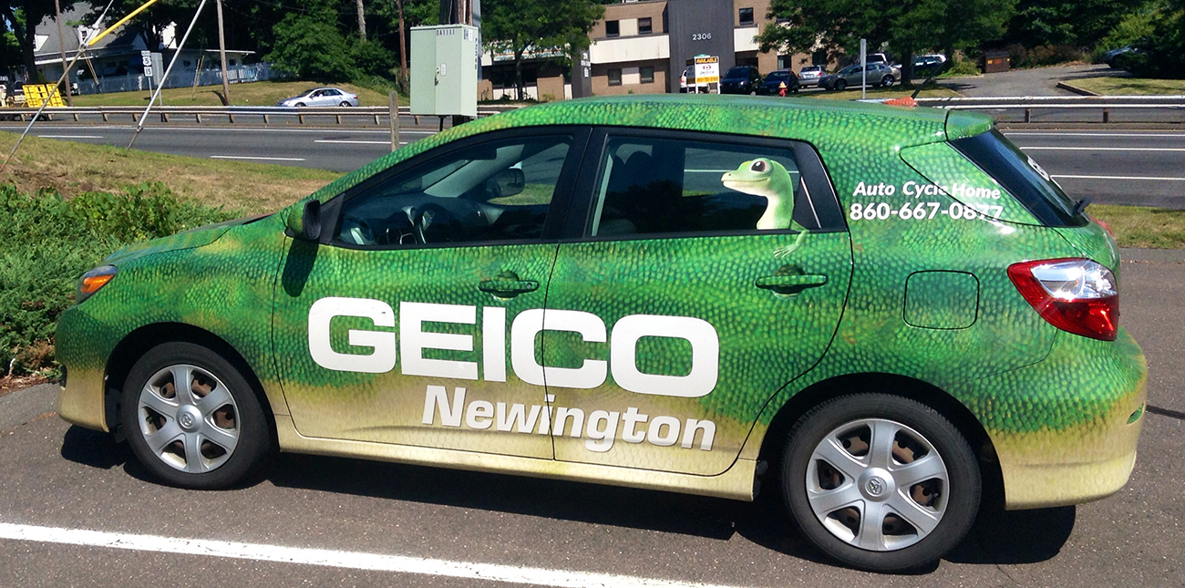 A photograph shows a car whose paint appears like the skin of a gecko. Large lettering reads Geico, and there is a decal of the Geico gecko on the window.