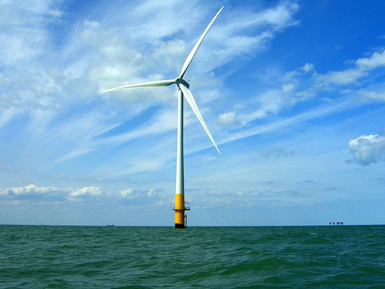 Wind turbine with three blades moored in shallow water.