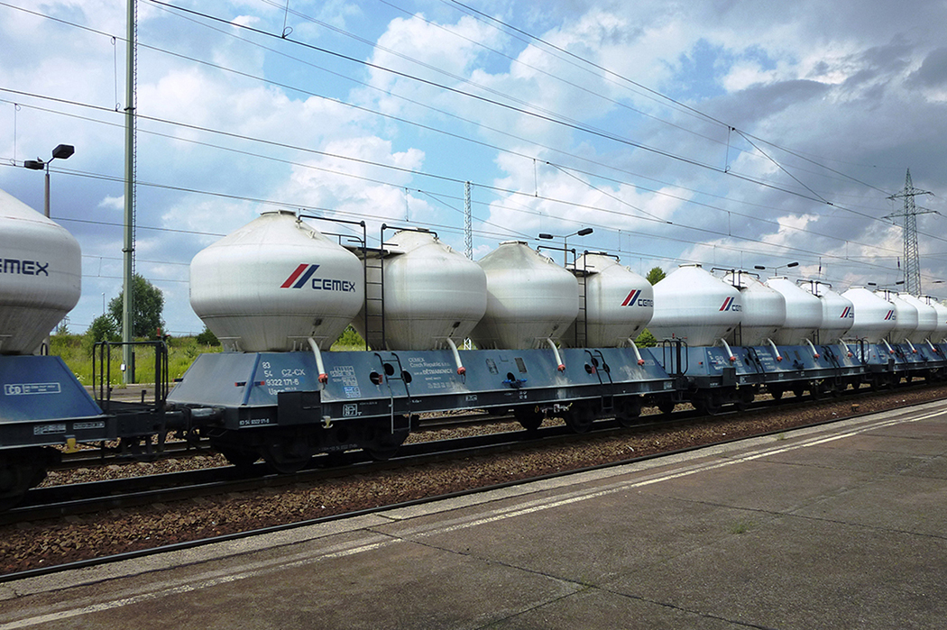 A photo shows the lateral view of a CEMEX's freight train with cement tank wagons running along a railway track.