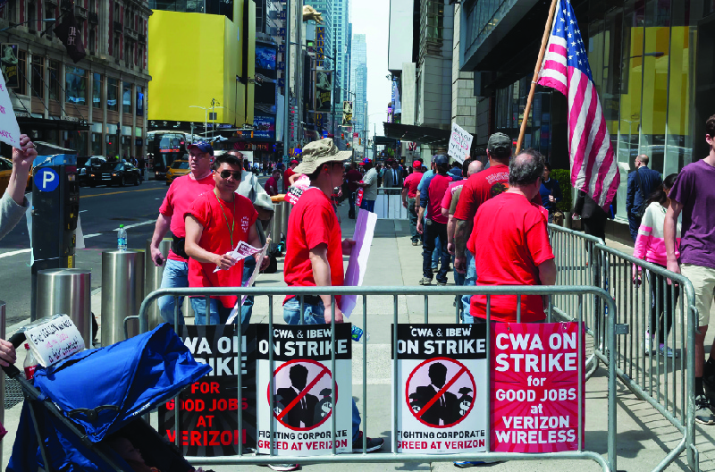 "This image shows a group of people dressed in matching red shirts in an area enclosed with signs that say ""CWA on strike for good jobs at Verizon Wireless"" and ""CWA and IBEW on strike. Fighting corporate greed at Verizon."""
