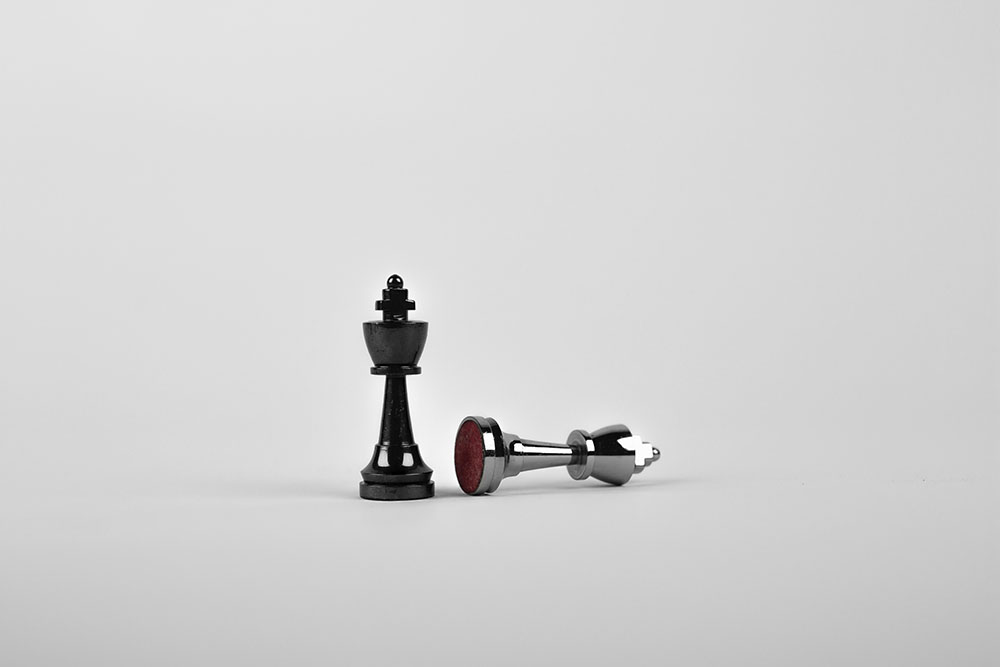 One chess piece stands upright next to another that lies on its side.