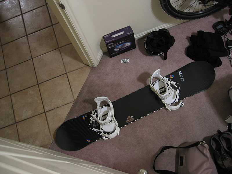 A photo shot from the above shows a snowboard featuring Flux premium bindings.