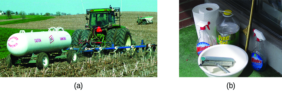 "This photograph shows a large agricultural tractor in a field pulling a field sprayer and a large, white cylindrical tank which is labeled ""Caution Ammonia."""