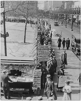 "A photograph shows a long line of men waiting on a New York City street for a hot meal. The man at the front of the line holds up a sign that reads, ""Line for 1 cent restaurant. 20 meals for 1 cent. Donations invited. Help feed the hungry. 1 cent will feed 20. 1 cent restaurant. 103 W. 43rd St."""