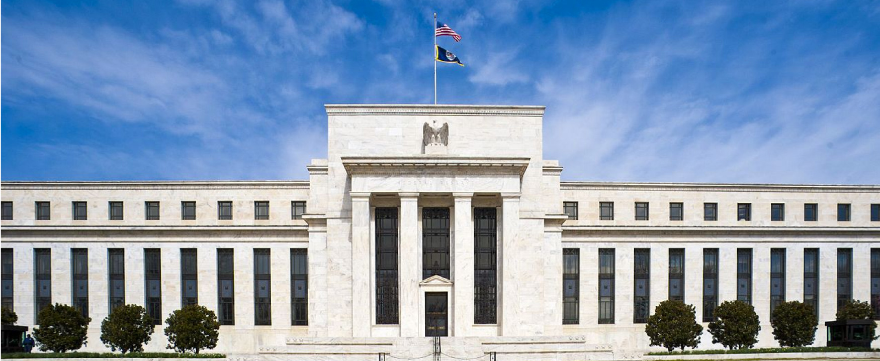 The Marriner S. Eccles Federal Reserve Board Building is shown.  The very large building, located in Washington DC, is constructed of white marble and has a grand entranceway.