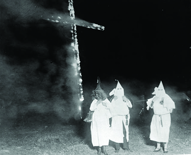 A photograph shows several hooded Klan members standing in front of a burning cross.