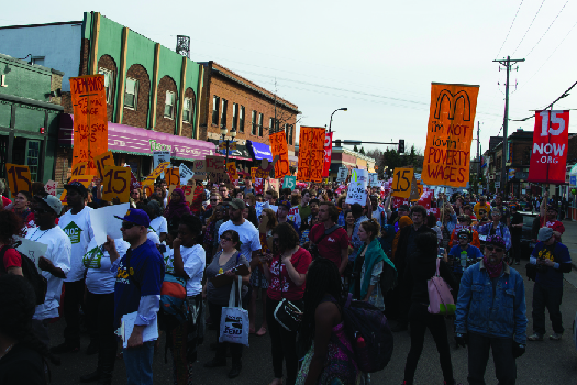 "An image of a group of people marching down a street, one of whom holds a sign that reads ""I'm not loving' poverty wages""."