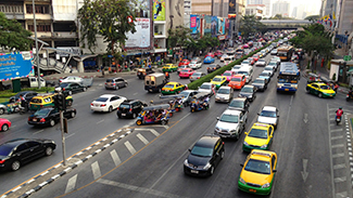 This is a picture of a city street with a traffic signal. The picture has very busy lanes of traffic in both directions.