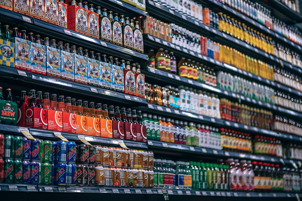 A photo shows store shelves with different bottles and cans of soft drinks.
